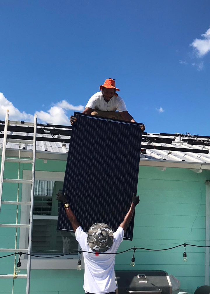 Solar Panel being lift to a Florida home rooftop by the May Custom Home team